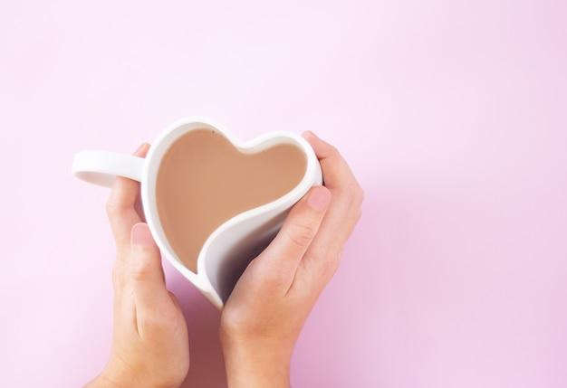 Mãos abraçam uma xícara branca em forma de coração cheia de café com leite
