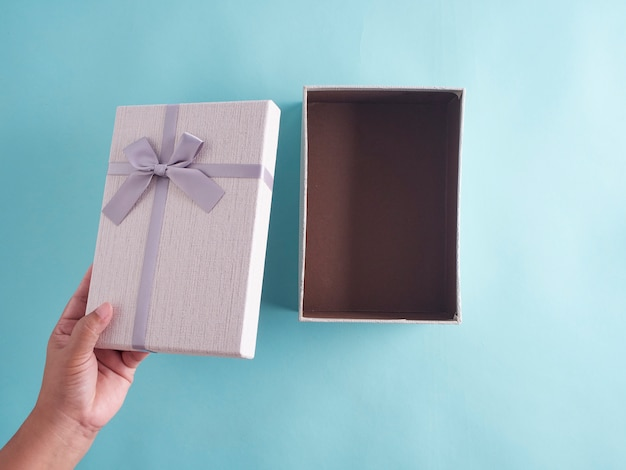Mãos abrindo a caixa de presente, vista superior.