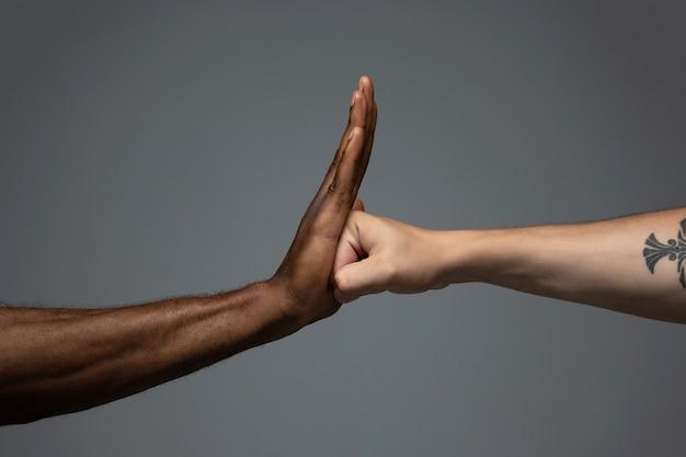 Mãos africanas e brancas gesticulando no fundo cinza do estúdio