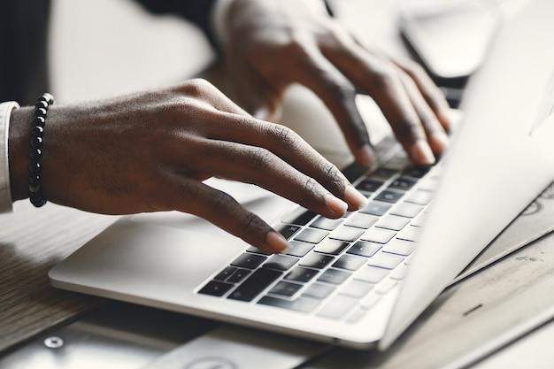 Mãos afro-americanas digitando em um laptop.