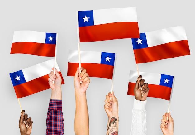 Mãos agitando bandeiras do chile