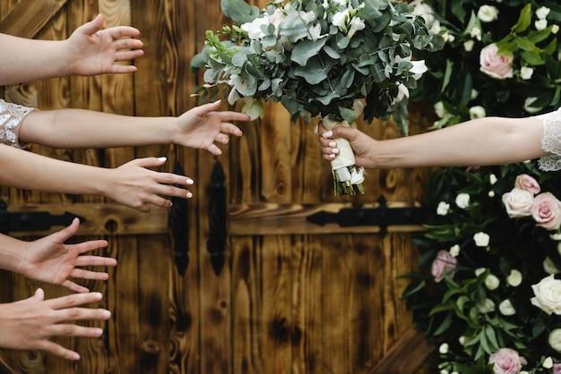 Mãos alcançando um buquê de casamento