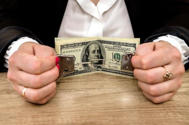 Mãos algemadas com notas de dólar
