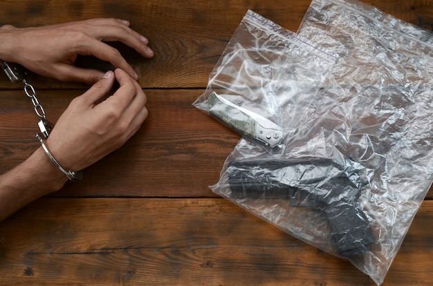 Mãos algemadas de suspeito criminal na mesa de madeira e arma com canivete em embalagens plásticas transparentes como evidência da cena do crime para investigação