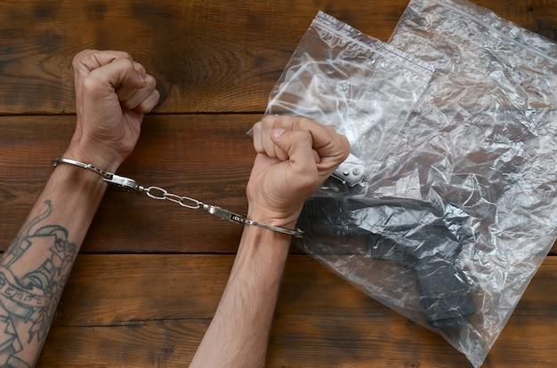 Mãos algemadas de suspeito criminal na mesa de madeira e arma com canivete