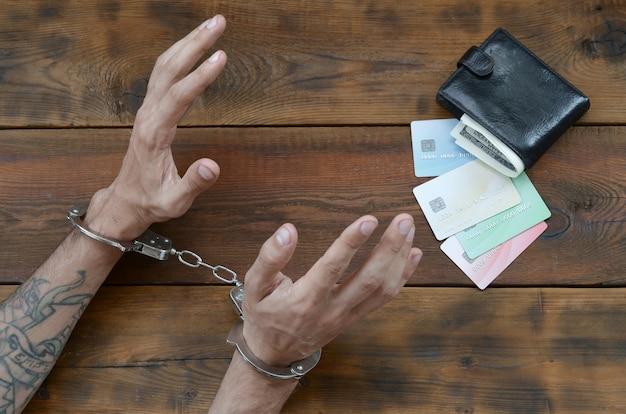 Mãos algemadas de suspeito criminal tatuado de cartões e cartões de crédito falsos