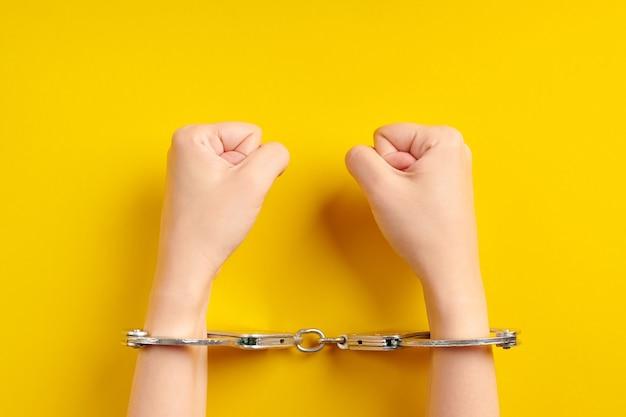 Mãos algemadas em fundo amarelo. conceito de prisão. privação da liberdade e apreensão dos perpetradores. fists.