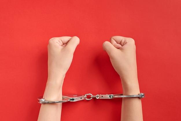 Mãos algemadas sobre fundo vermelho. conceito de prisão. privação da liberdade e apreensão dos perpetradores. fists.