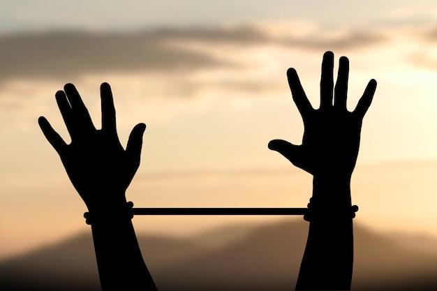 Mãos amarradas com corda contra corda escura do céu para a falta de liberdade