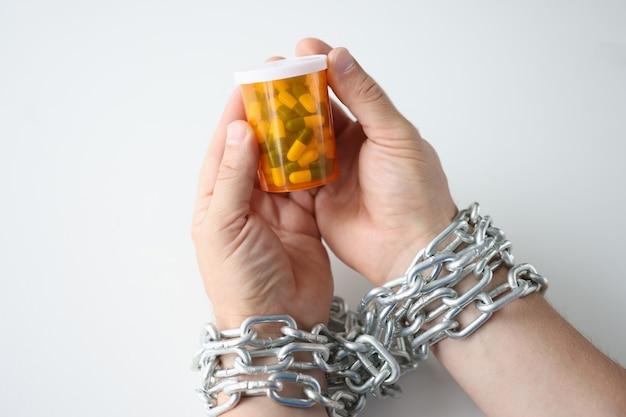 Mãos amarradas com corrente seguram o frasco do conceito de vício em drogas e medicamentos