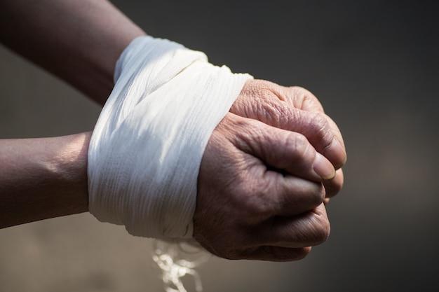 Mãos amarradas de uma mulher de meia-idade