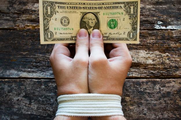 Mãos amarram homens e dinheiro nas mãos - um símbolo da escravidão