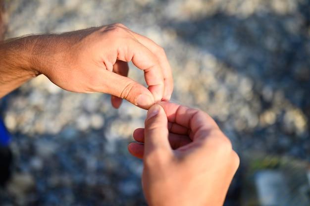 Mãos amarrando uma linha de pesca em um anzol
