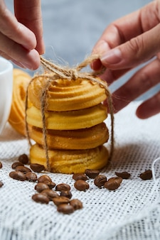 Mãos amarrando uma pilha de biscoitos com grãos de café.