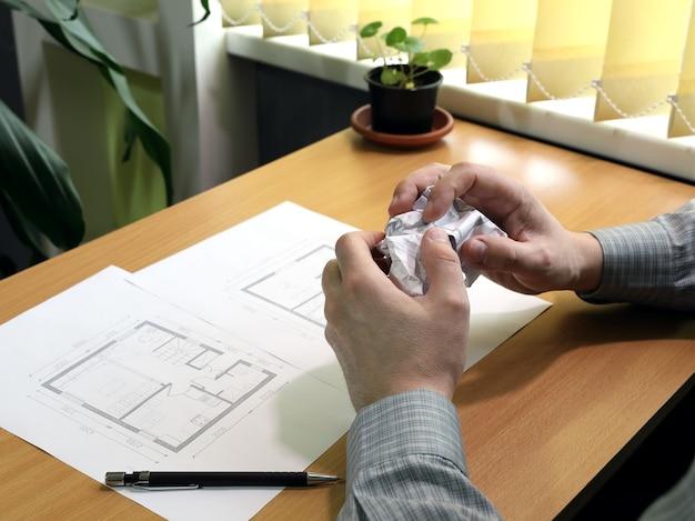 Mãos amassam uma folha de papel com erros