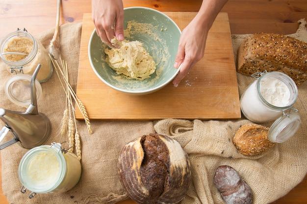 Mãos amassar massa para pastelaria caseira e pão