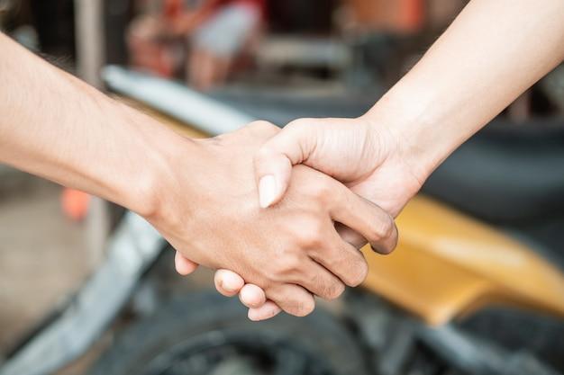 Mãos apertando as mãos contra o fundo da motocicleta na oficina de pneus
