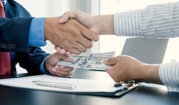 Mãos apertando funcionários do governo recebendo dinheiro de suborno de empresário conceito de corrupção