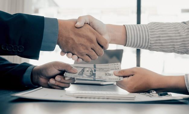 Mãos apertando funcionários do governo recebendo dinheiro de suborno de empresário
