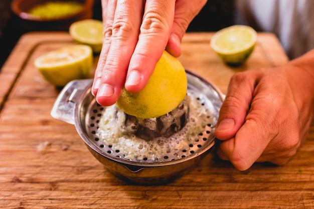 Mãos apertando o suco de limão.