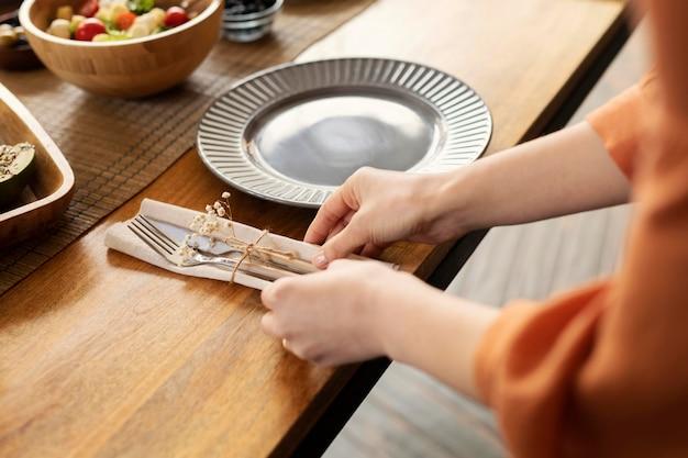 Mãos arrumando os talheres de perto