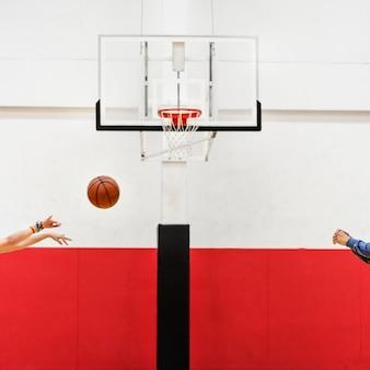 Mãos atirando basquete para o aro da rede