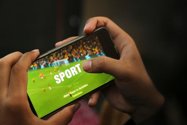Mãos atraentes jogando vídeo esporte em um telefone inteligente