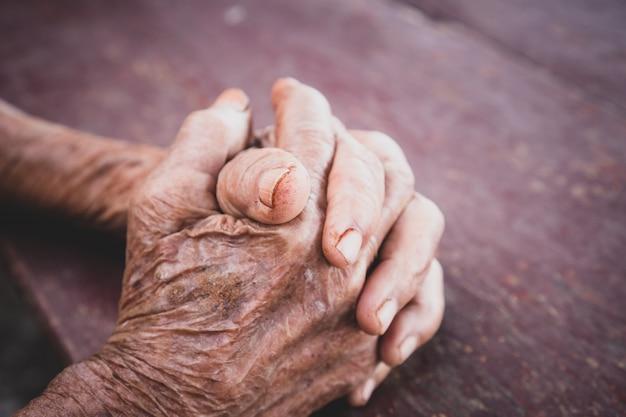 Mãos avó asiática idosa agarra a mão na mesa de madeira