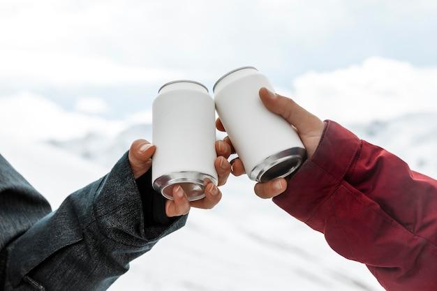 Mãos batendo latas de refrigerante perto