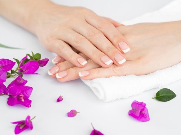 Mãos bem cuidadas da mulher delicada com flores