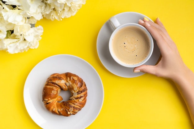 Mãos bem cuidadas da mulher segurando uma xícara de café sobre fundo amarelo. plano leigo, vista superior conceito de ramo de lançamento de café da manhã de verão primavera.