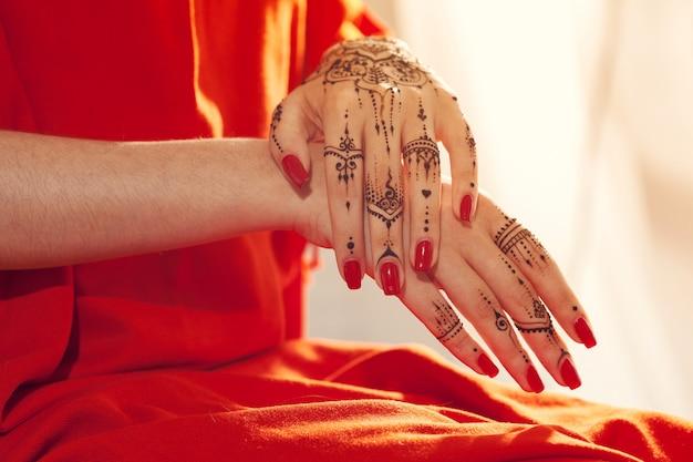 Mãos bem cuidadas vermelhas com mehndi