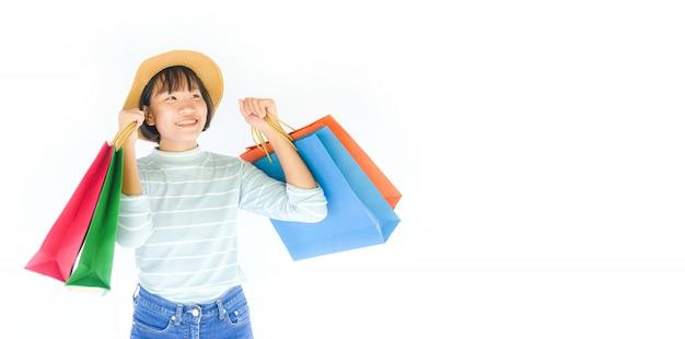 Mãos bonitas da menina da criança que mantêm o saco de compras isolado no fundo branco.