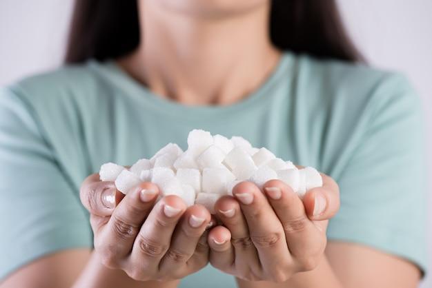 Mãos bonitas da mulher que guardam cubos do açúcar branco. conceito de saúde.