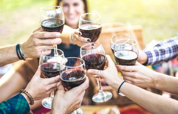 Mãos brindando vinho tinto e amigos se divertindo torcendo na experiência de degustação de vinhos