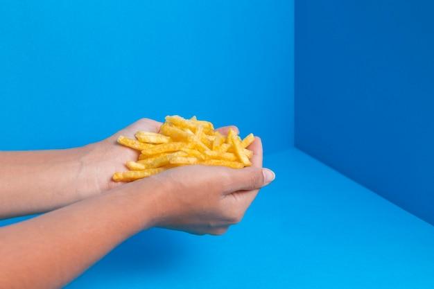 Mãos cheias de batatas fritas