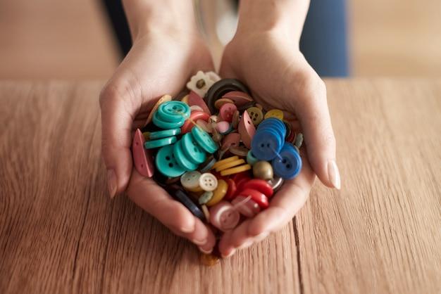 Mãos cheias de botões coloridos