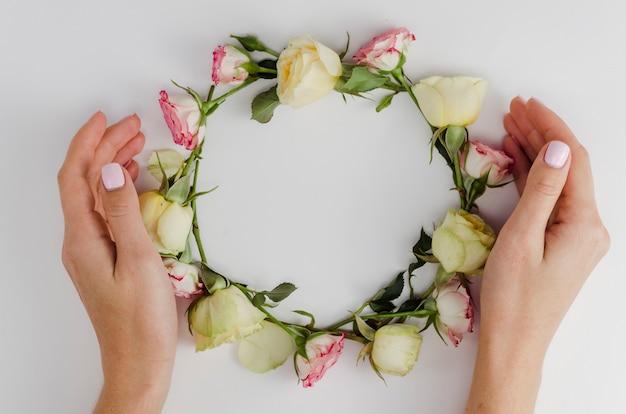 Mãos circundando moldura rosa redonda
