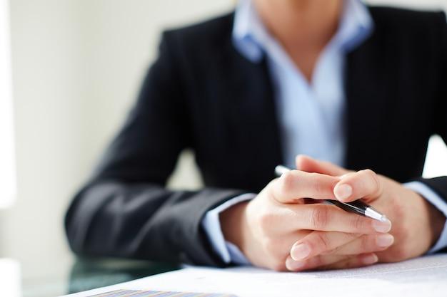Mãos close-up da mulher segurando uma caneta