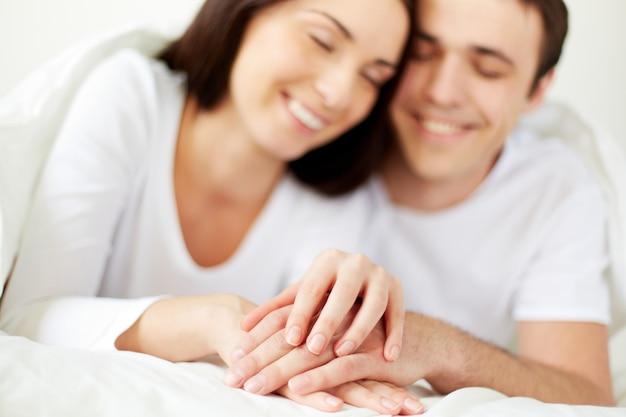 Mãos close-up de um casal na cama