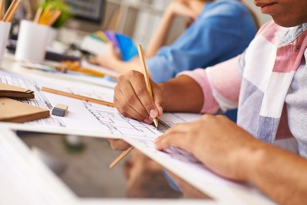 Mãos close-up de um menino trabalhando em seu projeto