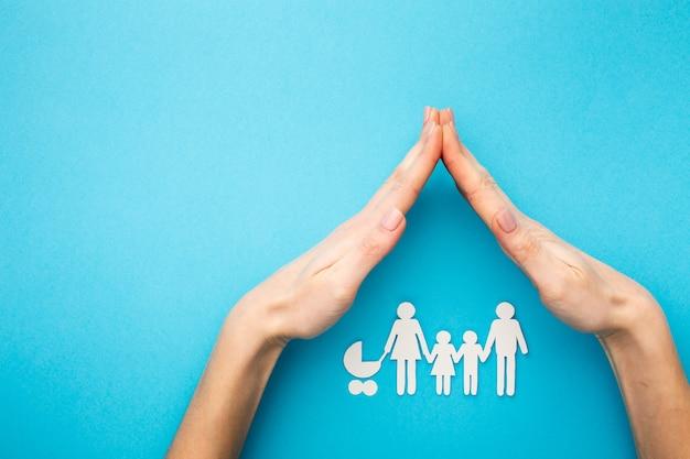 Mãos cobrindo a figura da família com espaço de cópia