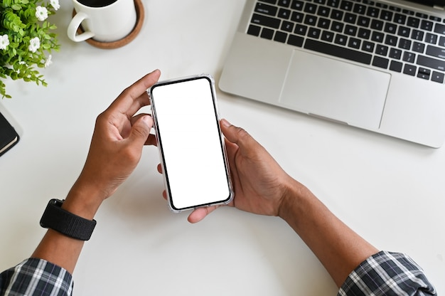 Mãos colhidas do tiro usando o smartphone do modelo na mesa de escritório com trajeto de grampeamento.
