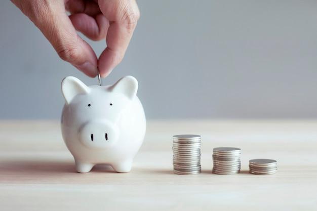 Mãos colocam moeda de dinheiro no cofrinho para economizar dinheiro, riqueza, finanças, economia, economia