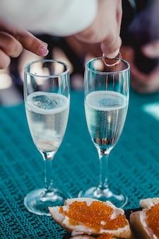 Mãos colocando anéis em taças de casamento com espumante champanhe
