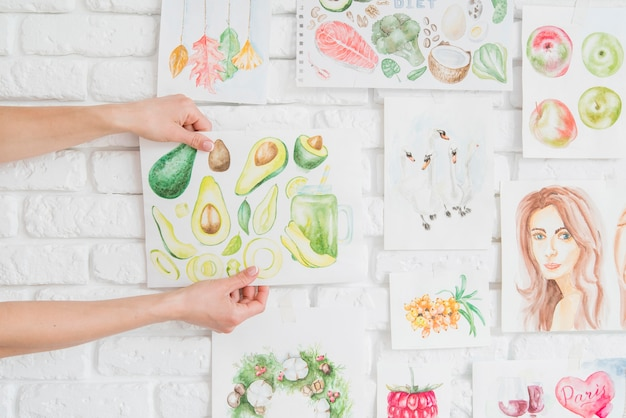 Mãos colocando frutas desenho na parede