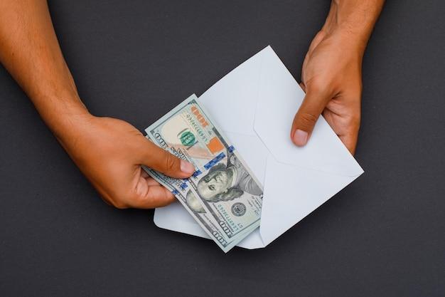 Mãos colocando notas em envelope.