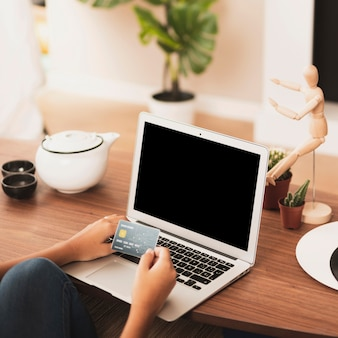 Mãos colocando um cartão em um laptop simulado
