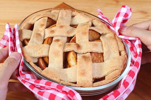 Mãos colocando uma torta de maçã caseira recém-assada na mesa da cozinha