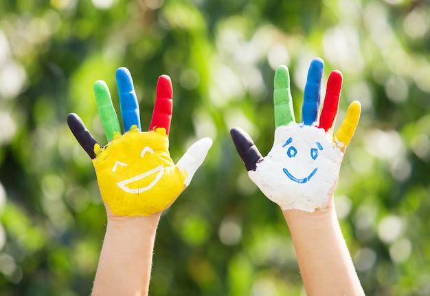 Mãos coloridas com sorriso pintadas em tintas coloridas contra o fundo verde do verão. conceito de estilo de vida